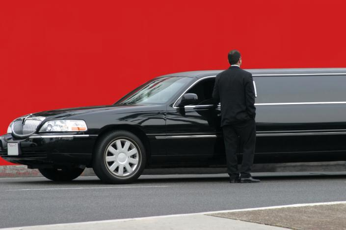 Elegant black stretch limousine with driver.