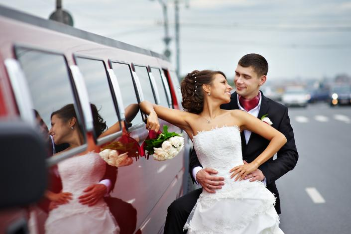 [Image: Bride & groom next to their Hummer Limousine.]